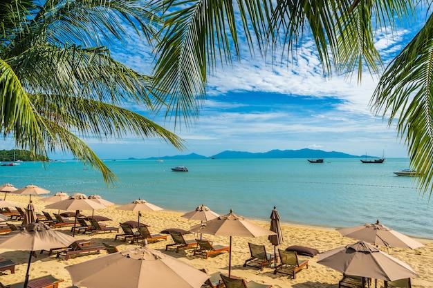 Belle Plage Tropicale Mer Et Océan Avec Cocotier Et Parasol Et Chaise Sur Ciel Bleu Photo gratuit