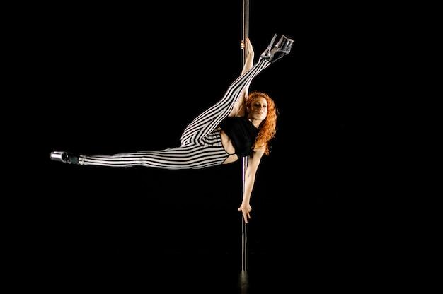 Belle et sexy femme rousse effectuant la pole dance Photo Premium