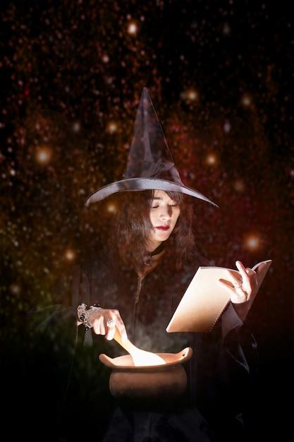 Une belle sorcière asiatique prépare une potion rougeoyante dans une marmite. Photo Premium