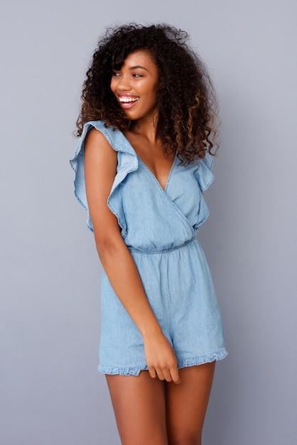 Belle souriante jeune femme noire contre le mur gris Photo Premium