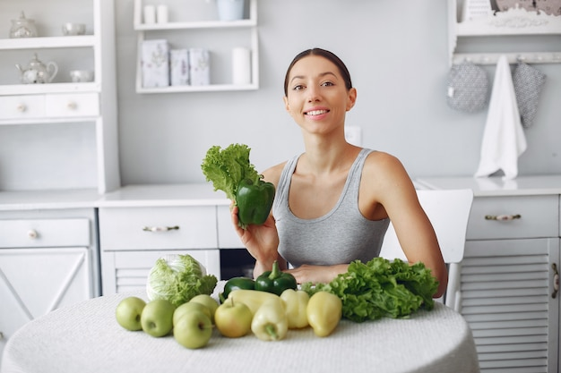 Belle et sportive femme dans une cuisine avec des légumes Photo gratuit