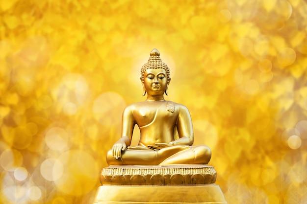 Belle statue de bouddha doré sur feuille de bokeh jaune doré feuille de pho (feuille de bo). Photo Premium