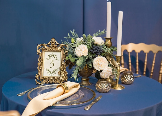 Belle table de mariage et décor de mariage avec des couverts dans les tons or et bleu foncé Photo Premium