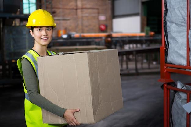 Belle Travailleuse Transportant Une Boîte Dans L'entrepôt Photo gratuit