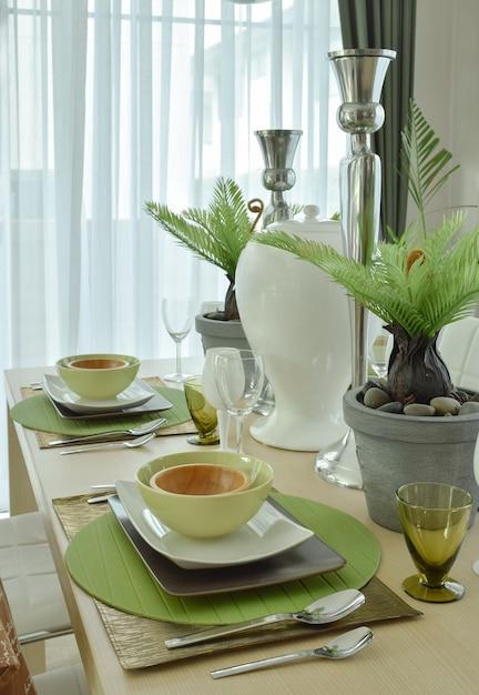 Belle vaisselle en céramique moderne dans l'arrangement de couleurs vert sur la table à manger Photo Premium