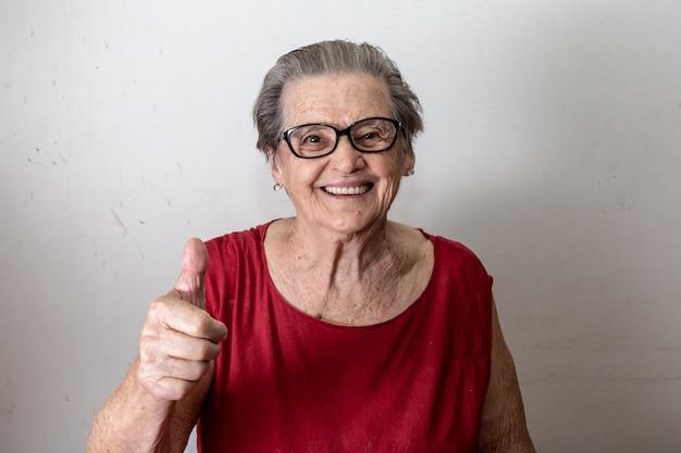 Belle vieille femme avec deux tumbs up. joyeux caucasien senior montrant deux pouces vers le haut sur fond blanc. Photo Premium