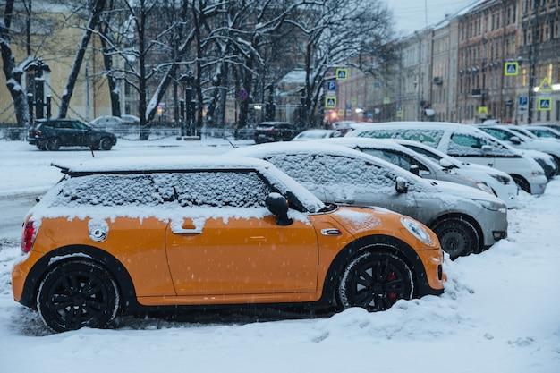 Belle ville enneigée pendant l'hiver. voitures sur un parking couvert de neige épaisse Photo Premium