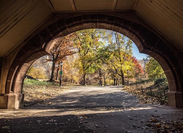 Belle Vue Sur Un Parc D'automne à Travers Une Arche De Pierre Photo gratuit