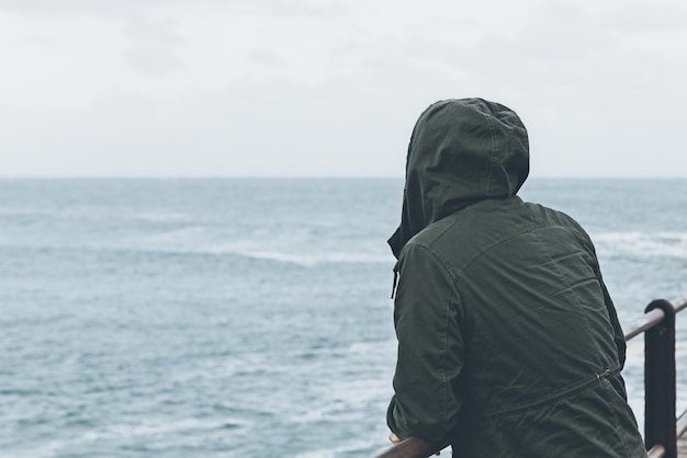 Belle Vue D'une Personne Debout Sur Le Quai En Regardant L'océan Par Temps Nuageux Photo gratuit