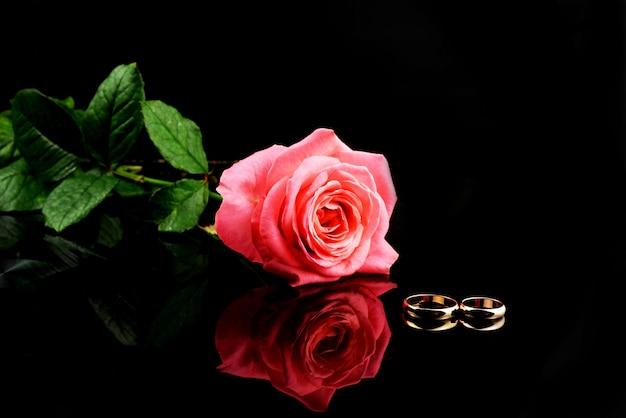 Belles alliances or pour les jeunes mariés avec une rose rose Photo Premium