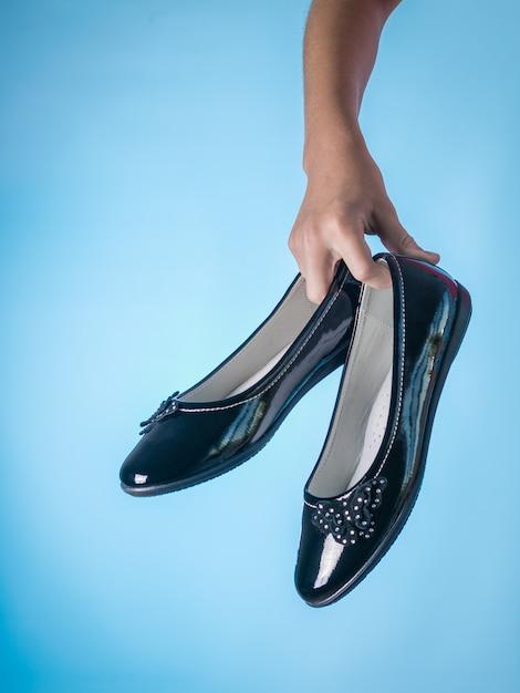 Belles Chaussures En Cuir Dans La Main D'un Enfant Sur Fond Bleu. Chaussures Pour Femmes En Cuir élégantes Et à La Mode. Photo Premium
