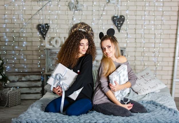 De belles copines avec des cadeaux pour le nouvel an dans leurs mains sont assises sur un plaid bleu et sourient. Photo Premium