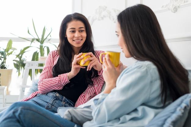 Belles copines parler et avoir une boisson chaude Photo gratuit