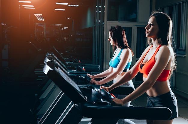 Belles Femmes Dans La Salle De Gym. Courir Sur Un Tapis Roulant Dans Un Club De Fitness Photo Premium
