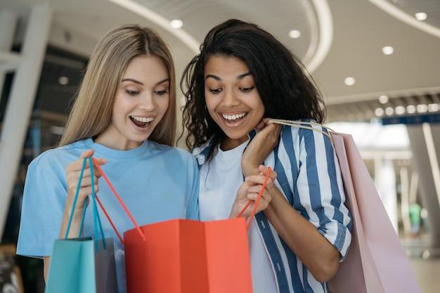 Belles Femmes émotionnelles Tenant Des Sacs à Provisions Dans Le Centre Commercial. Grand Concept De Vente Photo Premium