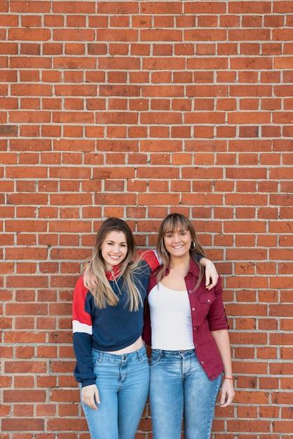 Belles femmes posant avec mur de briques Photo gratuit