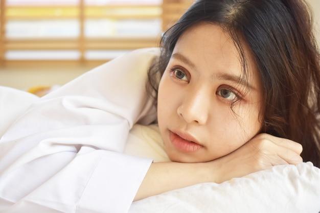 Belles femmes se réveillent et sur un lit blanc le matin Photo Premium