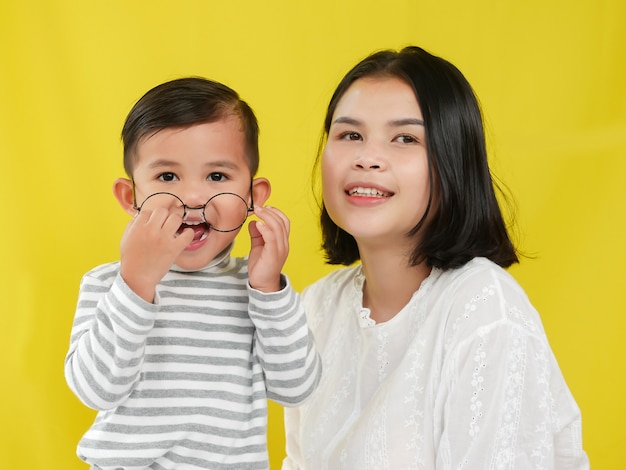 Belles femmes et son fils avec amour ensemble sur fond jaune. Photo Premium
