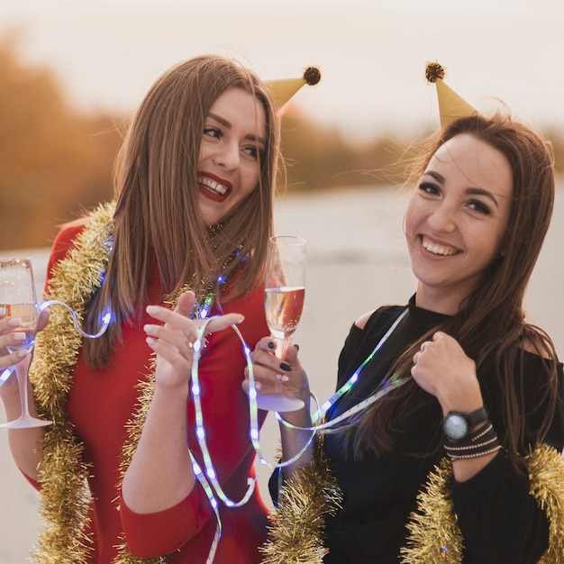 Belles femmes tenant des verres à champagne et des lampes sur la fête sur le toit Photo gratuit