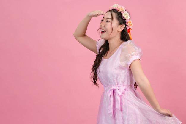 De belles femmes vêtues de belles robes de princesse roses sont debout sur un rose. Photo gratuit