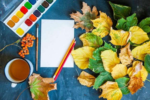 Belles feuilles d'automne, pinceaux, peinture et feuille sur noir Photo Premium