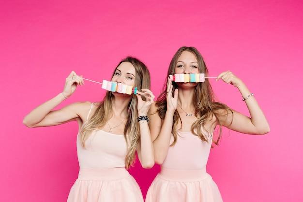 Les belles filles aiment les poupées s'amuser avec des bonbons à la guimauve sur un bâton. Photo Premium