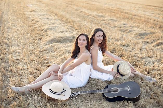 Belles filles élégantes dans un champ de blé en automne Photo gratuit