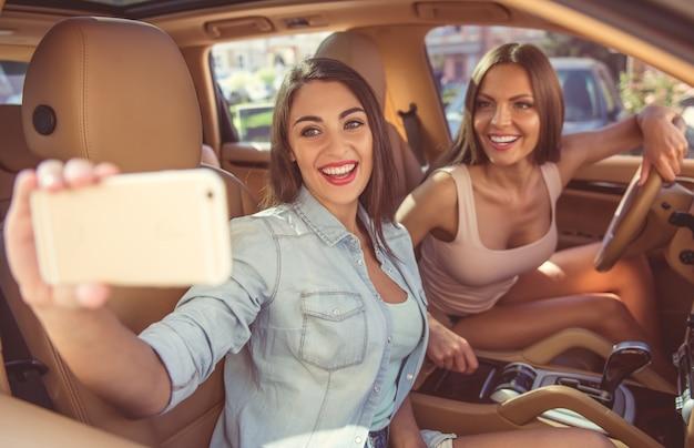 Belles filles élégantes font selfie en utilisant un smartphone Photo Premium