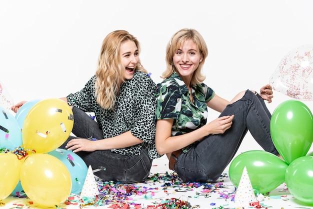 Belles filles entourées de confettis et de ballons Photo gratuit