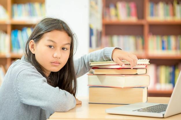 De belles filles lisent des livres dans des bibliothèques qui ont du mal à lire beaucoup de livres Photo gratuit