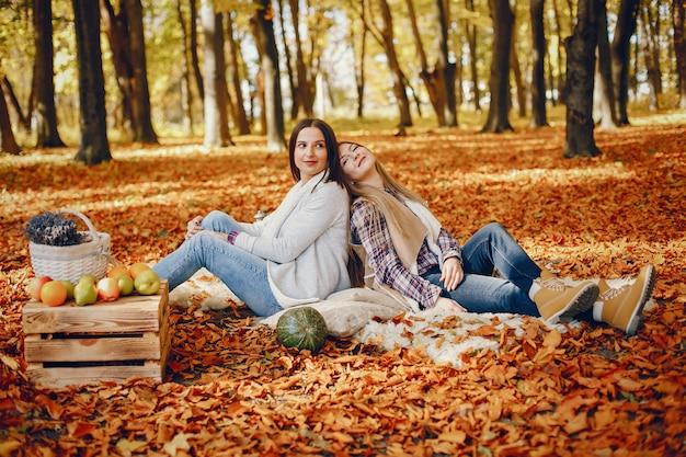 Belles filles s'amusent dans un parc en automne Photo gratuit