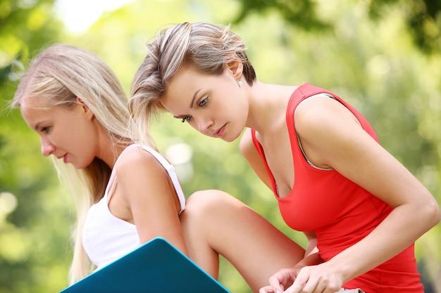 Belles filles utilisant des ordinateurs portables dans un parc Photo gratuit