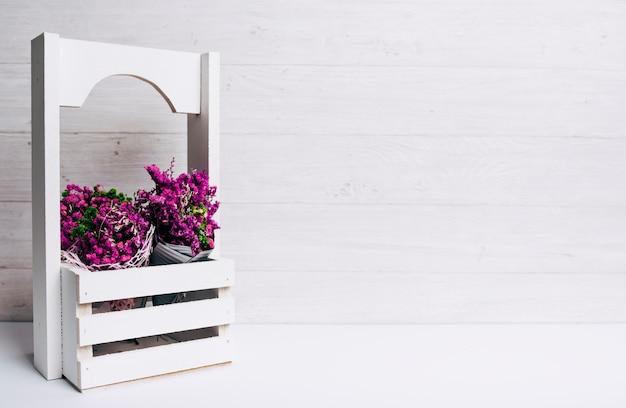 Belles fleurs mauves dans des caisses sur le bureau sur fond de bois Photo gratuit