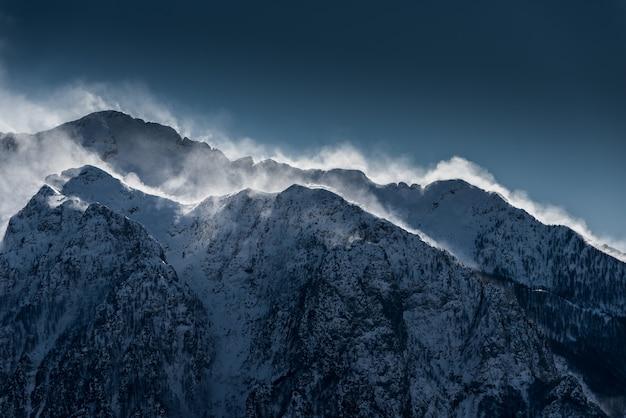 Belles Hautes Montagnes Enneigées Et Brumeuses Avec De La Neige Soufflée Par Le Vent Photo gratuit