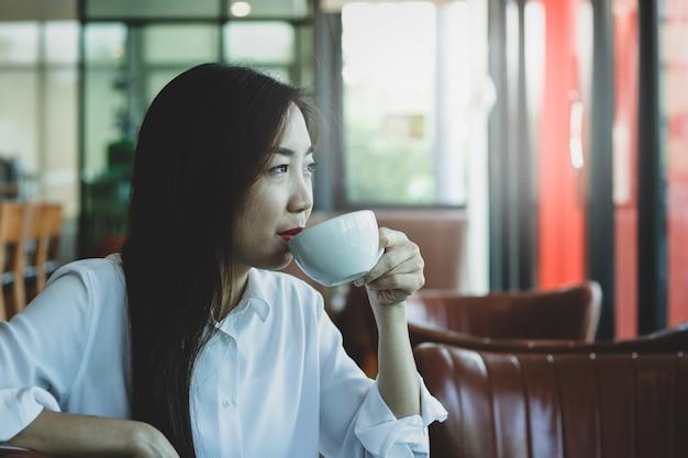 Belles jeunes femmes qui travaillent en sirotant un café dans un magasin de boissons Photo Premium
