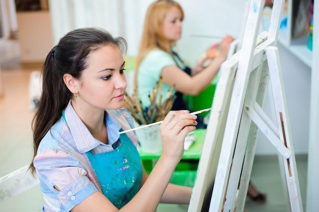 Belles jeunes filles dessine un tableau peint sur une leçon d'art Photo Premium