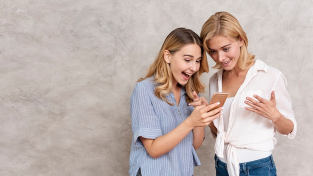 Belles jeunes filles vérifiant un message Photo gratuit