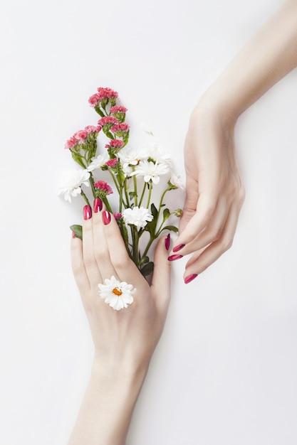 Belles mains bien entretenues fleurs sauvages sur la table Photo Premium