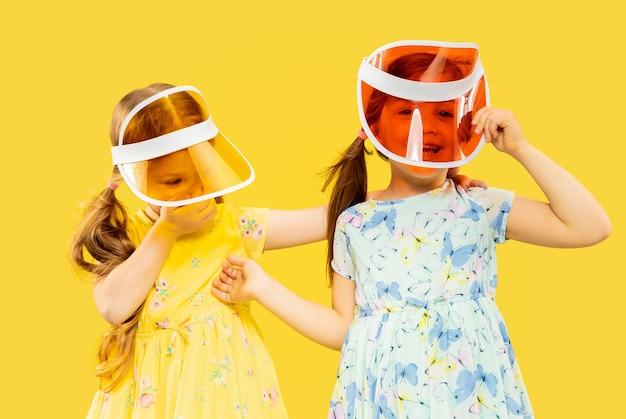 Belles Petites Filles émotionnelles Isolées. Portrait De Deux Sœurs Pleines De Bonheur Vêtues D'une Robe Et D'une Casquette. Concept D'été, émotions Humaines, Enfance. Photo gratuit