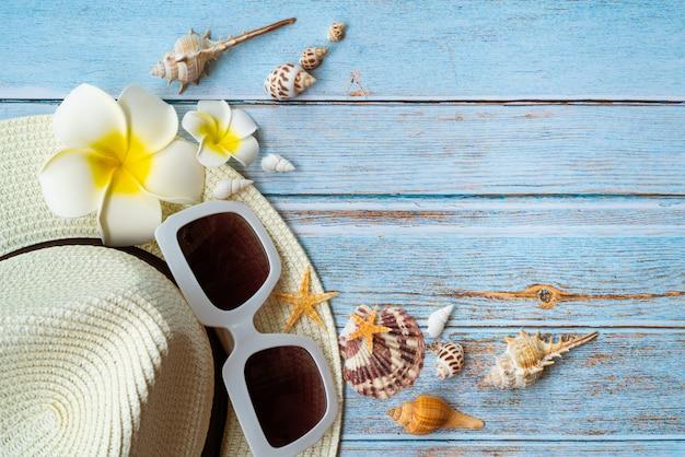 Belles vacances d'été, accessoires de plage, lunettes de soleil, chapeau et coquillages Photo Premium