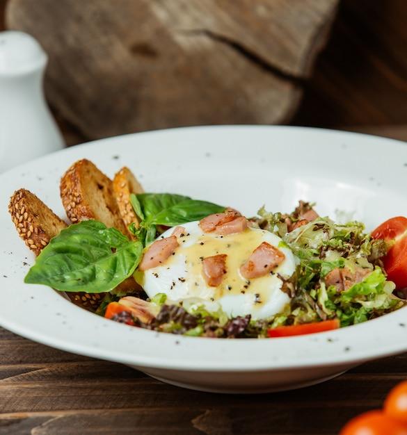 Bénédicte aux œufs servi avec des craquelins et une salade verte Photo gratuit
