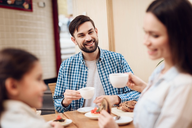 Bénédiction de la famille heureuse manger des gâteaux à la cafétéria. Photo Premium