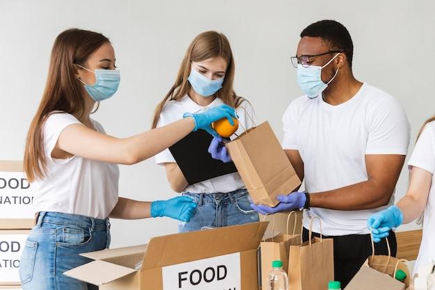Des Bénévoles Avec Des Gants Et Des Masques Médicaux Préparant Une Boîte Avec De La Nourriture Pour Le Don Photo gratuit