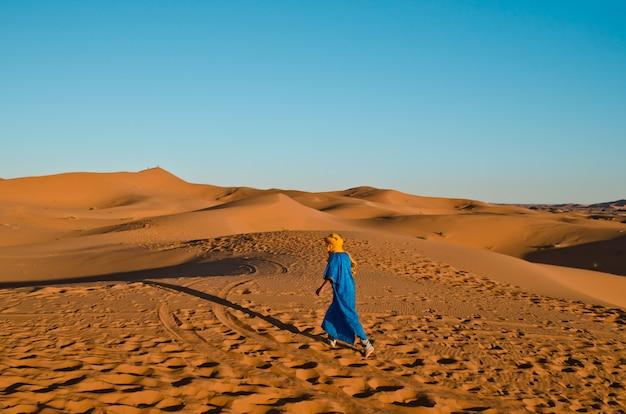 Berbère sur le dos marchant vers l'ombre d'une caravane de touristes montés sur un chameau Photo Premium