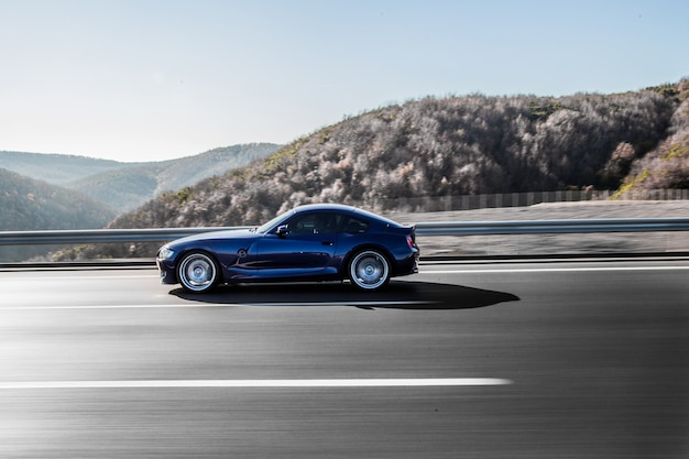 Une berline coupé bleu marine conduisant sur l'autoroute à travers les montagnes. Photo gratuit