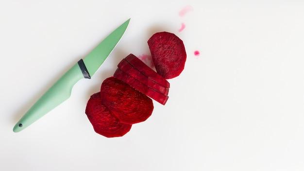 Betteraves tranchées à plat avec couteau vert Photo gratuit