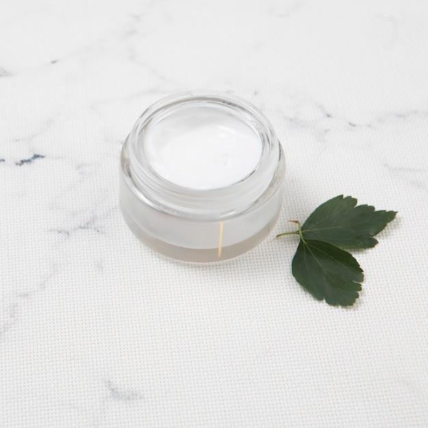 Beurre corporel avec des feuilles sur fond de marbre Photo gratuit