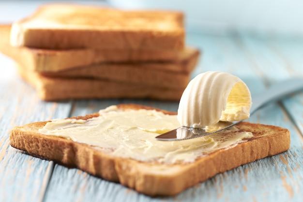 Beurre Et Tranches De Pain Grillé Sur Une Table En Bois Bleue. Photo Premium