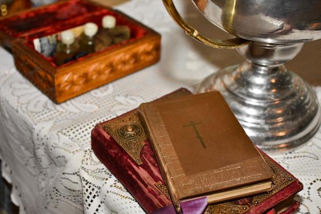 La bible repose sur la table avec la coupe dans l'église avant le rite du baptême Photo Premium