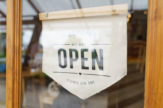 Bienvenue Signe Ouvert Large à Travers Le Verre De La Fenêtre Au Café. Magasin Prêt à Servir, Photo Premium